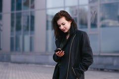 Retrato de una mujer morena sonriente hermosa joven que utiliza un teléfono móvil en un fondo de la ciudad Fotografía de archivo