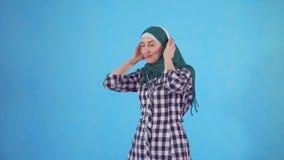 Retrato de una mujer musulmán joven con los auriculares que escucha la música y que baila en un fondo azul metrajes
