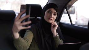 Retrato de una mujer musulm?n joven, atractiva que lleva un hijab que conmuta en un coche Ella es el llevar ropa oscura, sent?ndo almacen de video
