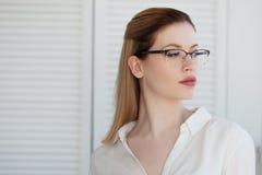 Retrato de una mujer de negocios elegante joven en una camisa blanca y vidrios imagen de archivo libre de regalías
