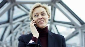 Retrato de una mujer de negocios hermosa joven en un traje trasero formal, sin los vidrios, caminando alrededor de la ciudad en almacen de video
