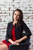 Retrato de una mujer de negocios morena de mediana edad en un vestido rojo corto y una chaqueta negra que se sientan en una silla fotografía de archivo