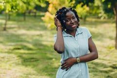 Retrato de una mujer negra joven sonriente de la belleza africana en un parque con la llamarada de la luz del sol y el espacio de fotos de archivo