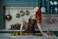 Retrato de una mujer pelirroja en la cocina fotos de archivo