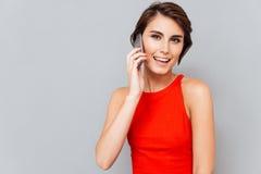 Retrato de una mujer preciosa feliz que habla en el teléfono Imágenes de archivo libres de regalías