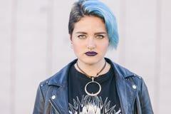 Retrato de una mujer punky joven con los ojos azules y el cuero oscuro c Fotos de archivo