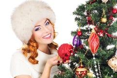 Retrato de una mujer que adorna un árbol de navidad Foto de archivo libre de regalías