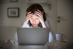 Retrato de una mujer que ase su cabeza cerca del ordenador portátil imagen de archivo