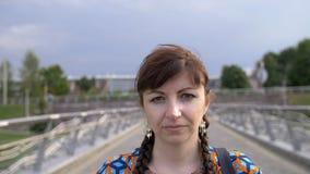 Retrato de una mujer que camina en el parque y que mira en la cámara foto de archivo