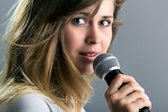 Retrato de una mujer que canta en el micrófono Imagen de archivo libre de regalías