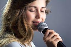 Retrato de una mujer que canta en el micrófono Foto de archivo libre de regalías