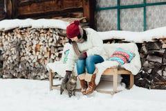 Retrato de una mujer que frota ligeramente un gato en la nieve Imágenes de archivo libres de regalías