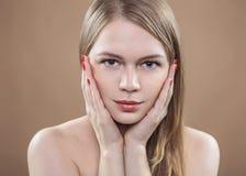 Retrato de una mujer que lleva a cabo una mano por su cara Ella tiene maquillaje diurno, la piel excelente, clavos rojos aseados  Imagen de archivo