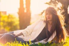 Retrato de una mujer que miente en el parque en la puesta del sol Imagenes de archivo