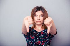 Retrato de una mujer que muestra los pulgares abajo Fotografía de archivo