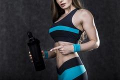 Retrato de una mujer que muestra una botella de agua Foto de archivo