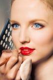 Retrato de una mujer que pone en trazador de líneas del labio. Fotos de archivo