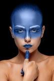 Retrato de una mujer que se cubre con la pintura azul Imagen de archivo libre de regalías