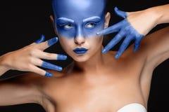 Retrato de una mujer que se cubre con la pintura azul Fotos de archivo libres de regalías