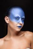 Retrato de una mujer que se cubre con la pintura azul Foto de archivo libre de regalías