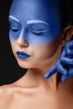 Retrato de una mujer que se cubre con la pintura azul Fotografía de archivo libre de regalías