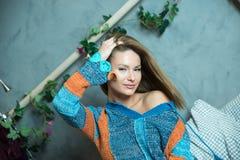 Retrato de una mujer que se sienta en una cama y que lleva un suéter Imagen de archivo