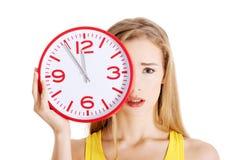 Retrato de una mujer que sostiene el reloj grande Imagen de archivo libre de regalías