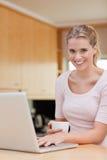 Retrato de una mujer que usa una computadora portátil mientras que bebe el café Foto de archivo libre de regalías