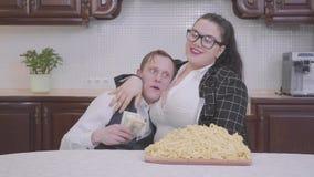 Retrato de una mujer regordeta confiada en la cocina en la tabla delante de una placa grande con los tallarines El abrazo de la m almacen de video