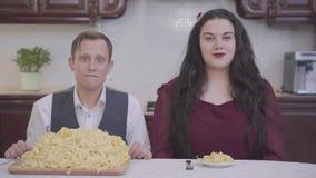 Retrato de una mujer regordeta elegante y de un empollón modesto que se sientan en una tabla delante de los tallarines en la coci almacen de metraje de vídeo