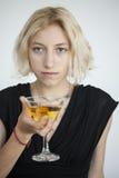 La mujer joven rubia con los ojos azules hermosos bebe un Martini Imagen de archivo libre de regalías