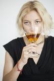 La mujer joven rubia con los ojos azules hermosos bebe un Martini Foto de archivo