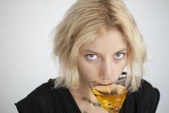La mujer joven rubia con los ojos azules hermosos bebe un Martini Fotografía de archivo
