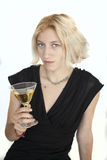 La mujer joven rubia con los ojos azules hermosos bebe un Martini Fotografía de archivo libre de regalías