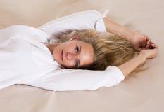 Retrato de una mujer rubia en cama Fotos de archivo