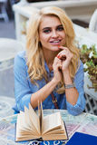 Retrato de una mujer rubia encantadora joven con la sonrisa hermosa que presenta mientras que se sienta con el libro en café de l Fotos de archivo libres de regalías