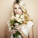 Retrato de una mujer rubia hermosa con las flores imagen de archivo libre de regalías