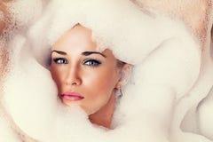 Retrato de una mujer rubia hermosa en la espuma Foto de archivo