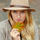 Retrato de una mujer rubia joven con las pecas que llevan un sombrero en t foto de archivo
