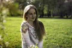 Retrato de una mujer rubia joven en un bosque de la primavera y en sunli Imagen de archivo libre de regalías