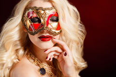 Retrato de una mujer rubia joven hermosa con la máscara de teatro en su cara en un fondo oscuro Foto de archivo