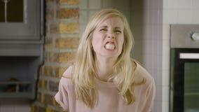 Retrato de una mujer rubia joven que ruge y que muestra sus dientes grandes en la cámara almacen de metraje de vídeo