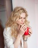Retrato de una mujer rubia joven que sostiene una taza roja que lleva una camisa blanca con una expresión de ser tristeza Hembra  Foto de archivo libre de regalías