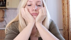 Retrato de una mujer rubia joven triste y aburrida que se sienta en concepto de la cocina, de la tristeza y de la depresión almacen de video