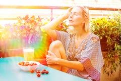 Retrato de una mujer rubia que se sienta en balcón imagenes de archivo