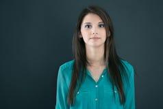 Retrato de una mujer seria joven aislada en un tablero negro imagen de archivo