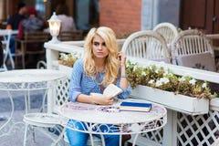 Retrato de una mujer soñadora encantadora joven que se sienta con los libros en café de la acera en día de primavera caliente, Fotografía de archivo