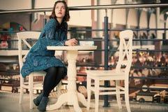 Retrato de una mujer soñadora joven que se sienta en el café Fotografía de archivo