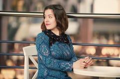 Retrato de una mujer soñadora joven que se sienta en el café Fotos de archivo
