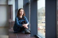 Retrato de una mujer soñadora joven que se sienta en el travesaño de la ventana Imágenes de archivo libres de regalías
